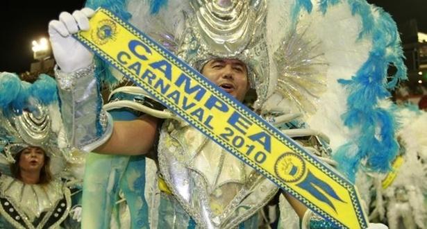 Integrante da Unidos da Tijuca exibe faixa de campeã do Carnaval 2010 no desfile das campeãs (20/02/2010)