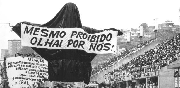 """Carro """"Cristo Mendigo"""" da escola de samba Beija-Flor de Nilópolis, envolto em plástico preto e com uma faixa com a inscrição """"Mesmo proibido, olhai por nós!"""", durante o desfile no sambódromo do Rio de Janeiro (7/2/1989)"""